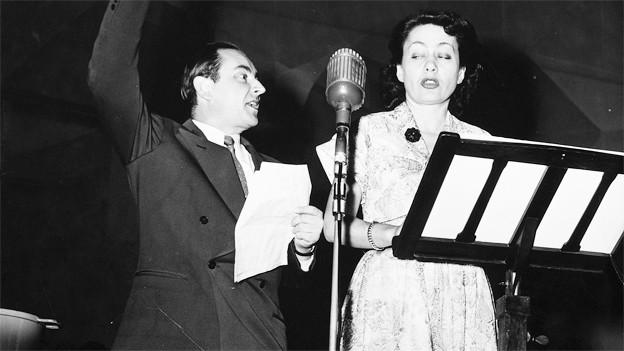 Ruedi Walter und Margrit Rainer stehend vor einem Mikrofon.