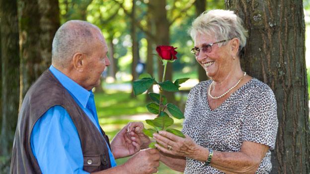 Senior erreicht Seniorin eine Rose im Wald.