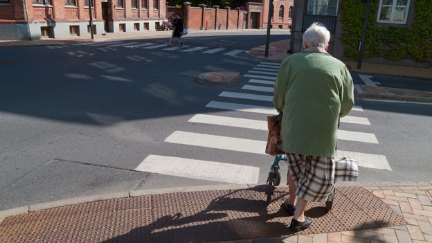 Seniorin will Zebrastreifen überqueren.