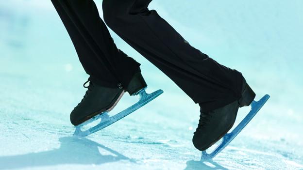 Beine und Schlittschuhe eines Eiskunstläufers, der zu einer Pirouette ansetzt.