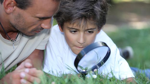 Vater und Sohn liegen im Gras. Der Sohn hält eine Lupe.