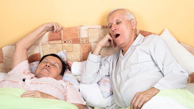Älteres Paar liegt lustlos und gähnend im Bett.