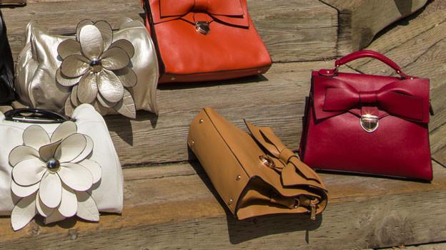 Mehrere Handtaschen liegen auf Treppe zum Kauf bereit.