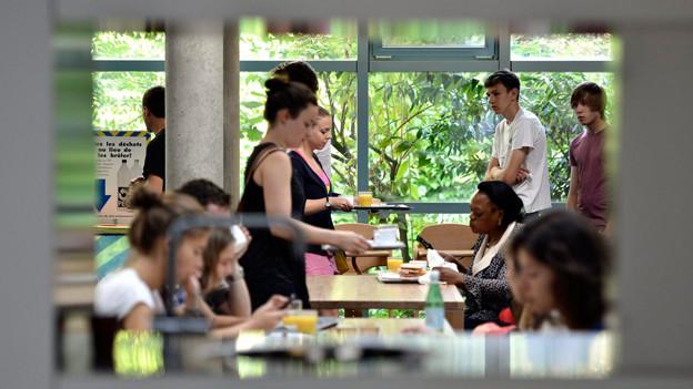 Junge Menschen beim Frühstück in einer Jugendherberge.