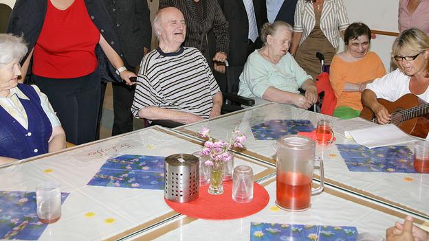 Ältere Menschen im Altersheim sitzen um gedeckten Kaffeetisch, singen und strahlen bis über beide Ohren.