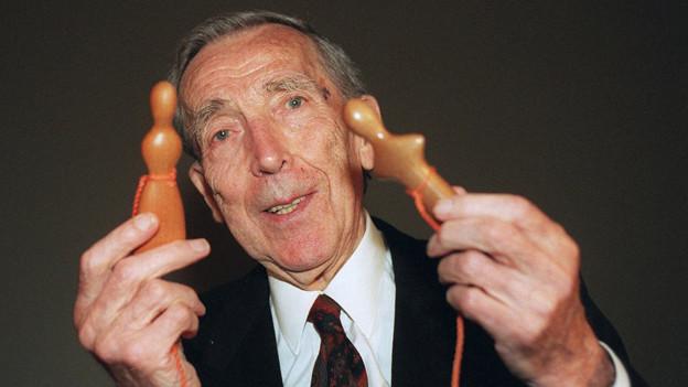 Antonio Vitali, im Alter von 90 Jahren, zeigt zwei seiner einfach geformten Holzfiguren, eine Frau und einen Mann.