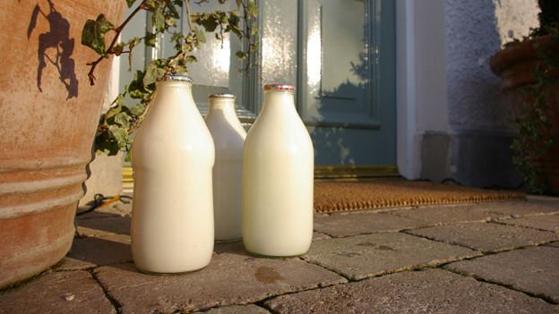 Drei Flaschen Milch stehen vor einer Haustür.