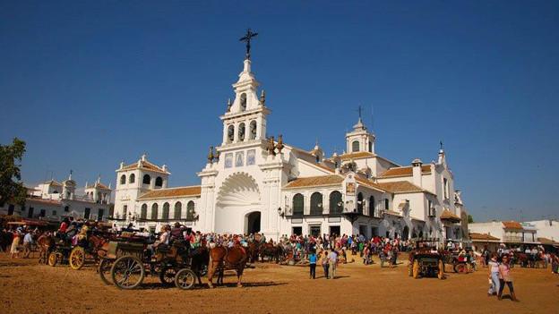 Auf dem Platz vor der Kirche in El Rocío versammlen sich an einem strahlenden Tag Pilgerinnen und Pilger.