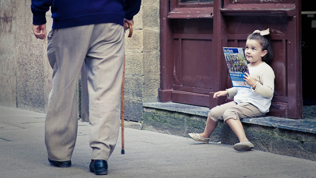 Mann geht mit Gehstock auf der Strasse. Ein kleines Mädchen sitzt auf einer Türschwelle, hält eine Zeitschrift in Händen und schielt dabei über den Rand um den älteren Mann zu beobachten.