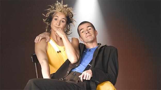 Ursus mit gelber Latzhose und wirrem Haar sitzt auf einem Stuhl, Ursus sitzt auf ihrem Schoss.