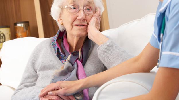 Fürsorglich legt eine Besucherin ihre Hand in jene einer bettlägrigen Seniorin.