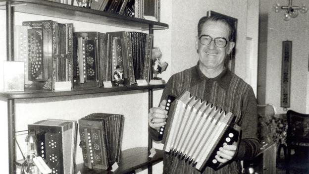 Schwarz-Weiss Fotografie von Max Weilemann in seinem Wohnzimmer. Auf einem Bücherregal reiht sich ein Langnauerli ans andere.