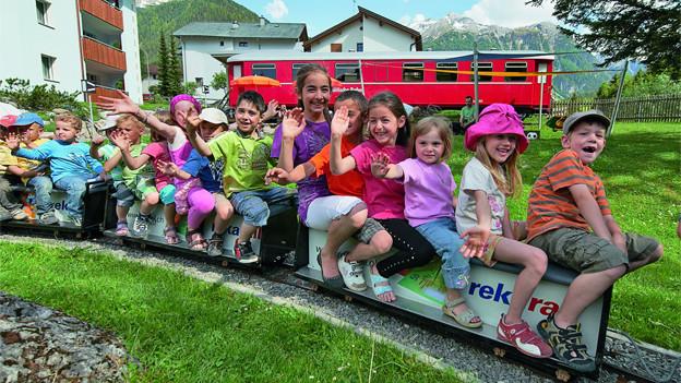 Eine Gruppe von fröhlichen Kindern sitzt auf Wagen eines kleinen Zugs, der durchs Feriendorf fährt.