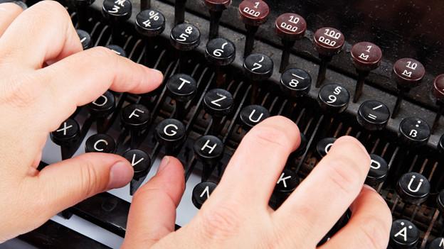 Frauenhände auf den Tasten einer mechanischen Schreibmaschine.