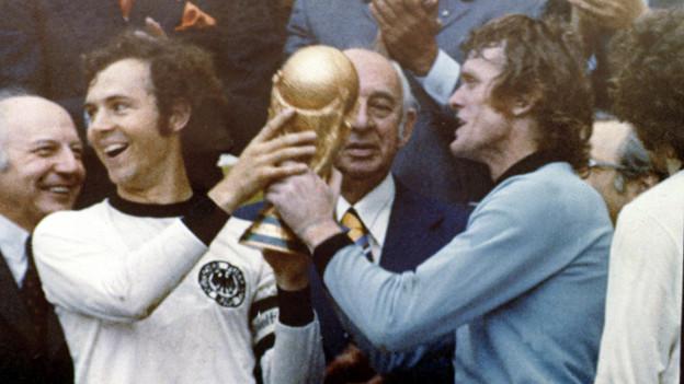 Verteidiger Franz Beckenbauer und Torwart Sepp Maier nach der Siegerehrung mit dem Weltmeister-Pokal.