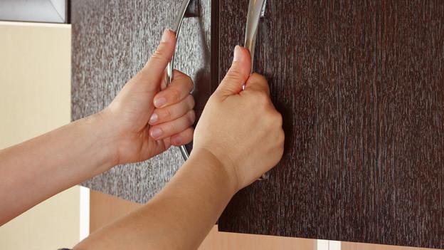 Hände einer Frau öffnen eine Küchenschrank-Türe.