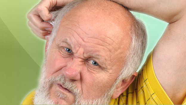 Bärtiger Senior kratzt sich an der Wange.