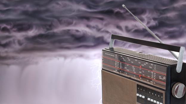 Ein älteres Radiomodell mit Antenne vor bedrohlicher Gewitterkulisse.