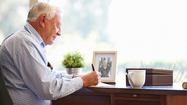 Ein älterer Mann sitzt am Schreibtisch und schreibt etwas auf ein Stück Papier.