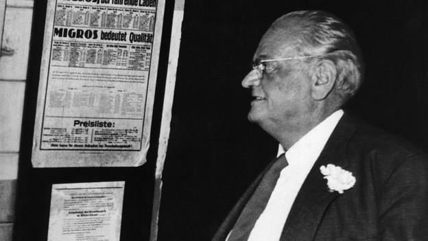 Gottlieb Duttweiler steht vor einem Zeitungsaushang auf dem steht: «Migros bedeutet Qualität».