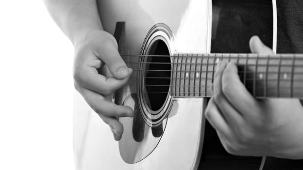 Schwarz-Weiss Fotografie von einer Gitarre während sie gespielt wird.