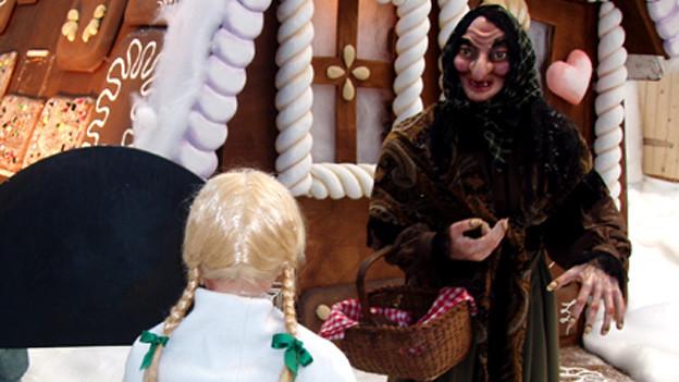 Holzfiguren von Hexe und Gretel vor Knusperhäuschen.