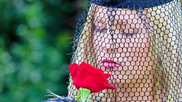 Trauernde Frau mit schwarzem Schleier vor Gesicht riecht an roter Rose.
