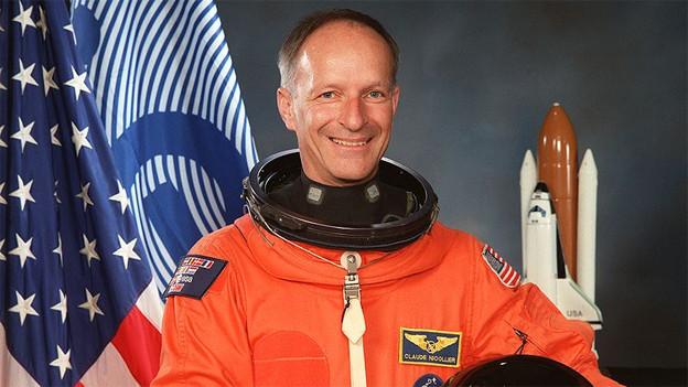 Der Astronaut mit orangem Astronauten-Anzug und schwarzem Helm vor einer amerikanischen Flagge.
