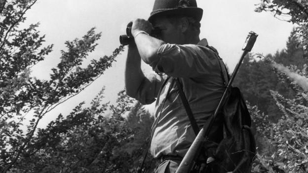 Die Schwarz-Weiss Fotografie zeigt einen Jäger mit Feldstecher und über die Schulter gehängtem Gewehr.