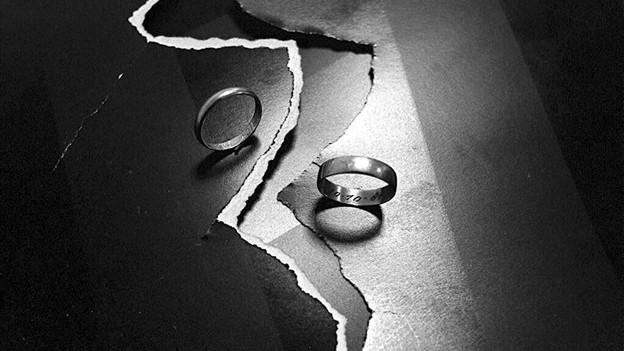 Schwarz-Weiss Fotografie mit zwei Eheringen, die links und rechts von zerrissenem Papier liegen.