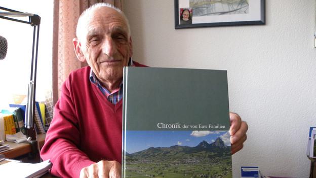 Der Senior zeigt am Wohnzimmertisch das von ihm verfasste Buch mit der Familienchronik.
