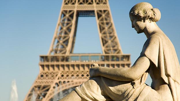 Statue einer sitzenden Frau mit Blick auf den Eiffelturm.