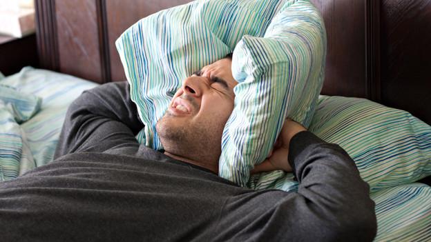 Ein Mann hält sich das Kissen vor die Ohren.
