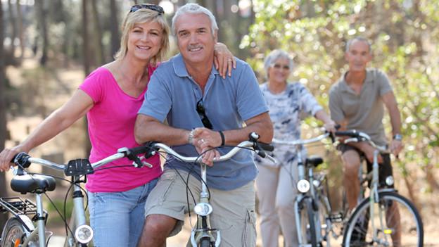 Zwei Senioren-Pärchen unternehmen einen Ausflug per Fahrrad.