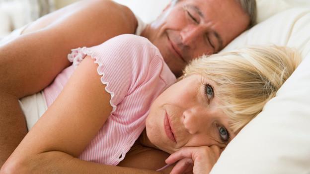 Seniorenpaar liegt in Bett. Er schläft, sie liegt verärgert wach.