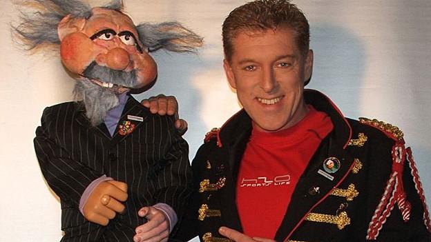 Roli Berner mit Puppe (älterer Mann im Anzug mit Bart und wirrem Haar).