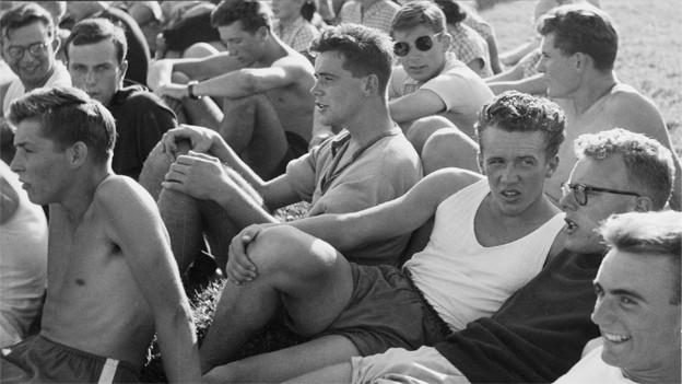 Schwarz-Weiss Fotografie mit jungen Männern in Sporbekleidung, die auf einem Rasen sitzen.