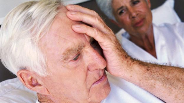 Senioren im Bett. Mann hat offensichtlich Schmerzen, er hält sich die Hand and en Kopf. Frau daneben schaut ihn mitleidig an.