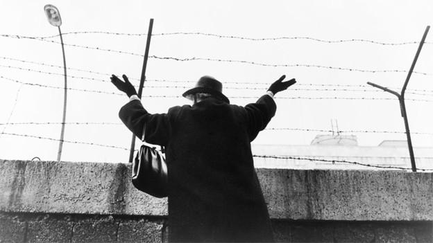 Schwarz-Weiss Fotografie von einer Frau, die über die mit Stacheldraht versehene Mauer blickt und winkt.