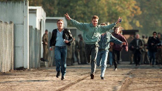 Drei junge Männer laufen fröhlich über die Grenze, einer hält seine Arme freudig in die Luft.