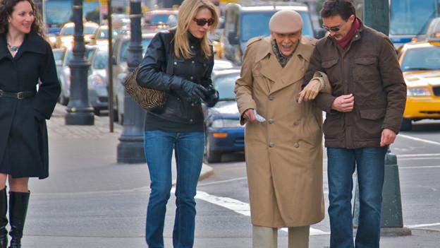 Zwei junge Menschen helfen Senior über die Strasse.