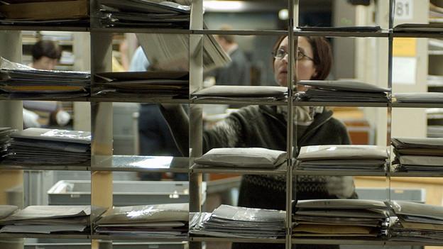 Eine Frau hinter einem Regal mit Briefen in der Hand, die sie in verschiedene Fächer verteilt.