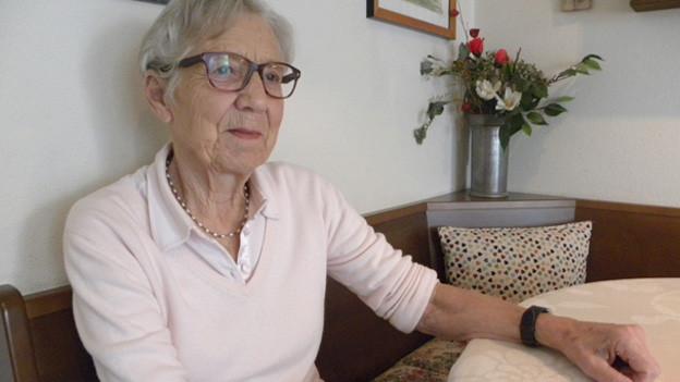 Elena Sacchi sitzt an ihrem hölzernen Küchentisch auf Holzbank in ihrer Wohnung in Zürich. Sie ist eine ältere Dame (83).