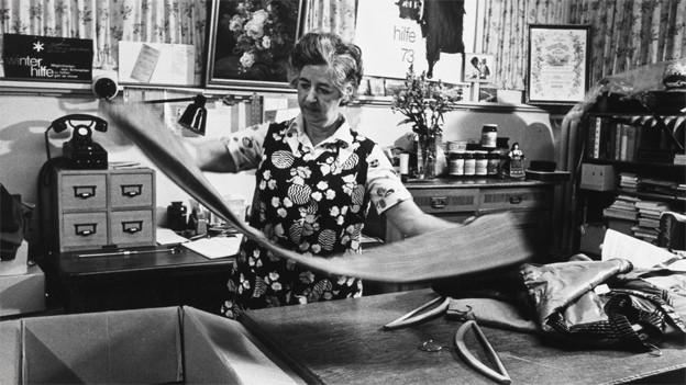 Schwarz-Weiss Fotografie. Eine Frau faltet eine Hose zusammen, die sie einem Karton entnommen hat.