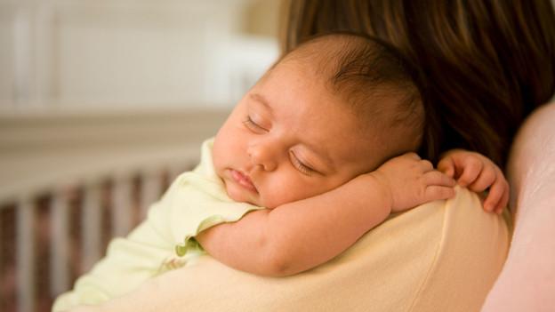 Ein Baby schläft zufrieden auf den Schultern einer dunkelhaarigen Frau.
