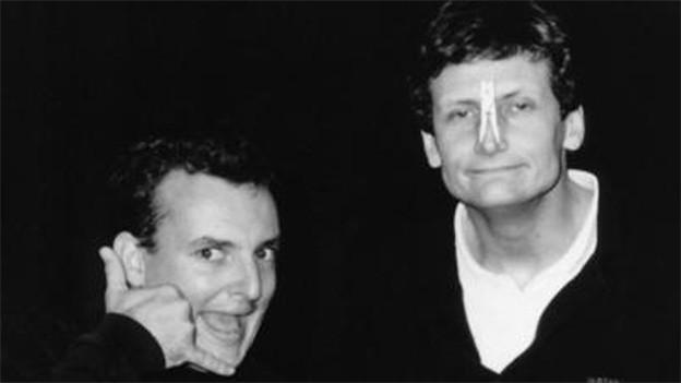Schwarz-Weiss Fotografie der beiden Kabarettisten, die lustige Grimassen ziehen.