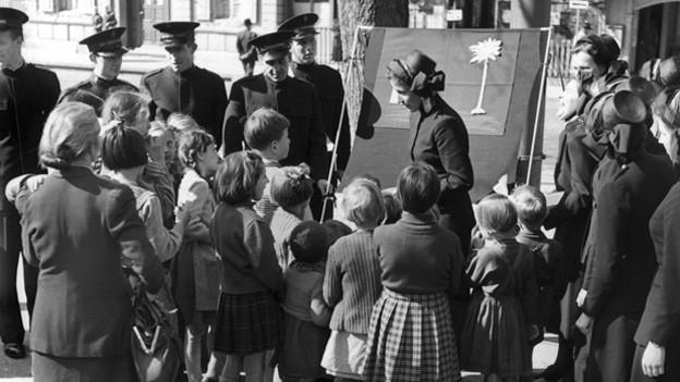 Altes Bild aus den Fünfziger Jahren. Eine Soldatin der Heilsamree und mehrere Kadetten stehen vor einem selbstgebastelten Plakat und sprechen mit einer Kinderschar die sie mit neugierigen Blicken begutachtet.