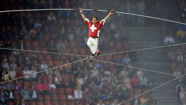 Der Hochseilartist trägt ein T-Shirt mit Schweizer Kreuz und weisse Hosen. Er balanciert auf Seilen, die quer durchs Stadion gespannt sind.