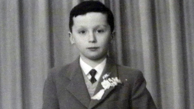 Ein etwa elfjähriger Junge im Anzug mit Krawatte.