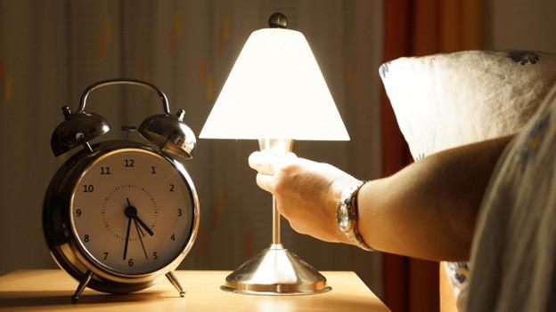 Mit einer Hand wird die Nachttischlampe eingeschaltet. Der Wecker auf dem Nachttisch zeigt halb fünf.
